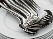 Pile of plates with spoons and forks