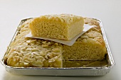 Bee sting cake with flaked almonds in baking tin, partly sliced