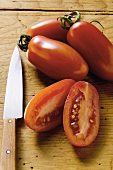 Four grape tomatoes on wooden background, one halved