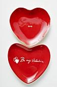 Rote herzförmige Teller mit Schrift Be my Valentine und Love
