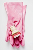 Pink rubber gloves and brush