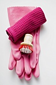 Pink rubber gloves, brush and tea towel