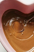 Chocolate fondue with heart-shaped chocolate on fondue fork