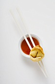 One deep-fried wonton with sweet and sour sauce