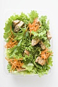 Salad leaves with carrots and croutons in take-out box