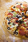 Pepperoni pizza with peppers and olives on wooden plate