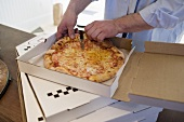Man taking piece of pizza Margherita out of pizza box