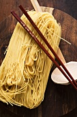 Egg noodles on wooden plate with chopsticks and ladle