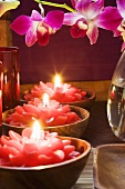 Thai table decoration: red flower candles and orchids