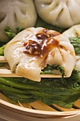 Yeast dumplings with chive filling on pak choi (Thailand)