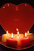 Burning candles and heart-shaped plate for Valentine's Day