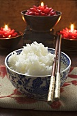 Bowl of rice in front of burning candles (Asia)