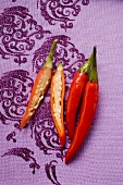 Red chili peppers on purple fabric, one cut open