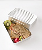 Ham sandwiches, radish and kiwi fruit in lunch box
