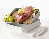 Ham sandwiches, radish and grapes in lunch box