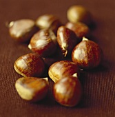 Sweet chestnuts on brown background