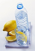 Mineral water in bottle and glass and lemon wedges