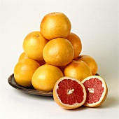Pink grapefruits on plate, one cut open in front