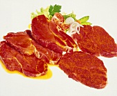 Raw, seasoned pork steaks; salad