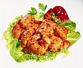 Raw, seasoned chicken piece on lettuce leaves
