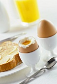 Boiled eggs with & without tops  in egg cups, buttered toast
