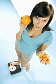 Young woman standing on scales with crisps and orange