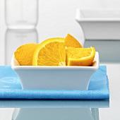 Orange quarters in a small bowl
