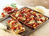 Pizza with vegetables and ham on baking tray