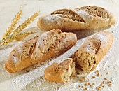 Three white bread sticks, beside wheat grains and ears