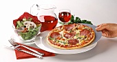 Salami pizza with salad and red wine