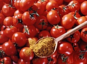 Vine tomatoes, curry powder on wooden spoon above