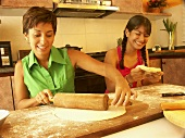 Young woman and girl making pastry (rolling out)