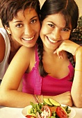 Young woman and girl in front of mixed salad