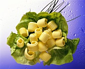 Several butter curls arranged on a lettuce leaf