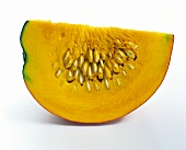 Segment of orange pumpkin with seeds on white background