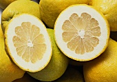 Several whole pomelos and two pomelo halves (close-up)