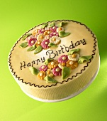 Cake with marzipan flowers and the words 'Happy Birthday'
