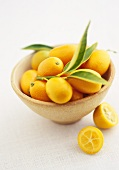 Kumquats in a bowl with two halves beside it