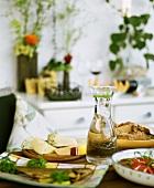 Käse, Fisch, Brot & Tomatensalat auf einem Tisch angerichtet