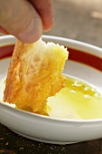 Hand dipping a piece of white bread into a bowl of olive oil
