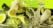 Pieces of leek falling into water against green background