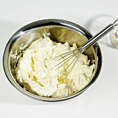 Cheesecake mixture being mixed with a whisk