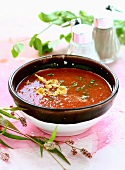 Tomato soup in a brown-rimmed bowl