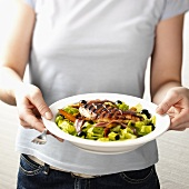 Woman holding a salad with barbecued chicken fillet