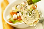White wine being poured into white wine glass, salad behind