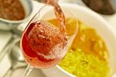 Rosé wird in ein Glas gegossen, dahinter Curryhühnchen