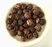 Black peppercorns in a white dish