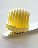 A butter curl on a knife (close-up)