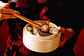 Woman taking food from steaming basket with chopsticks