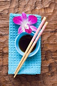 Still life with soy sauce, chopsticks, orchid & hand towel